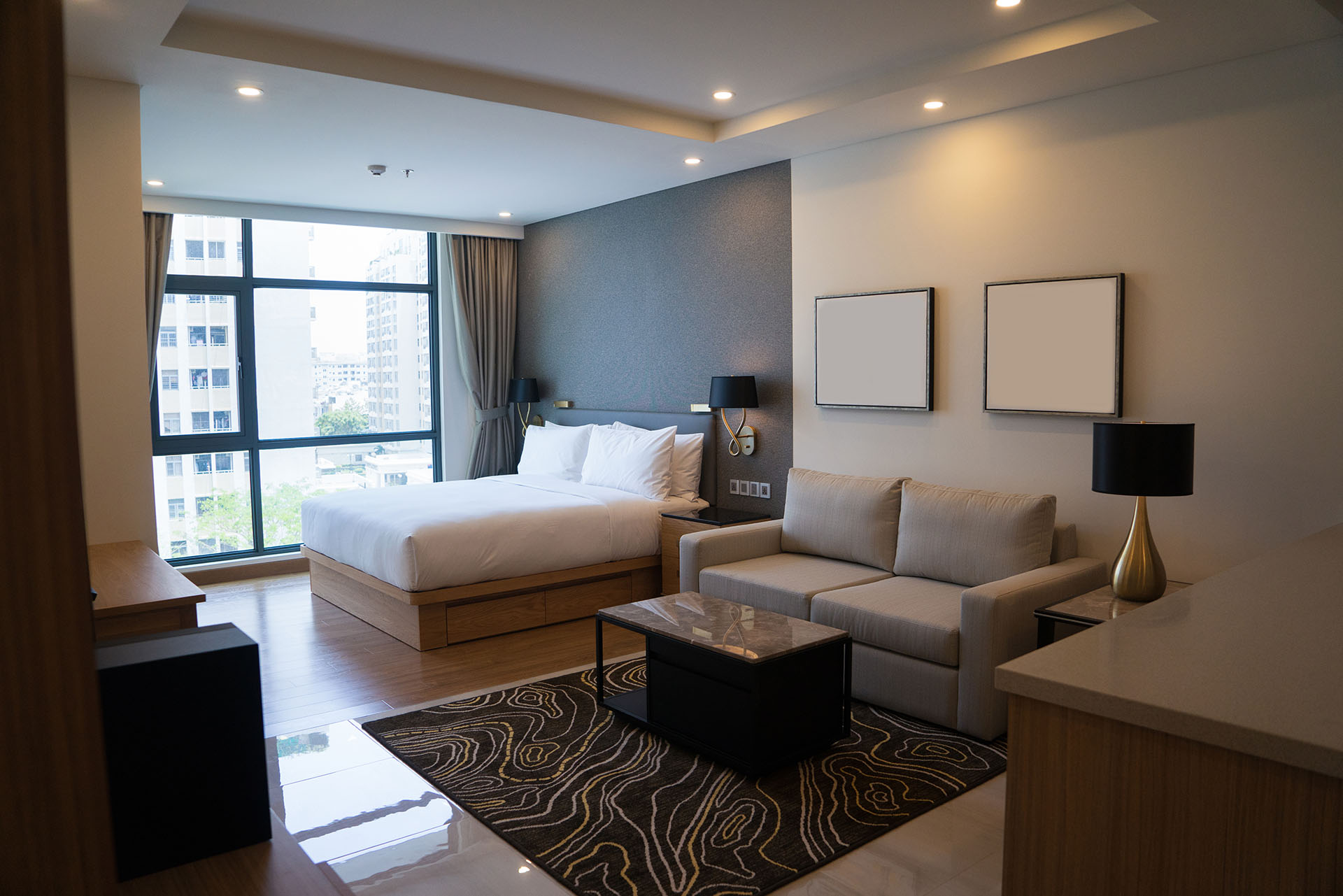 Cozy studio apartment design with bedroom and living space. Hotel room panoramic window, double bed, sofa and coffee table. Urban apartment concept